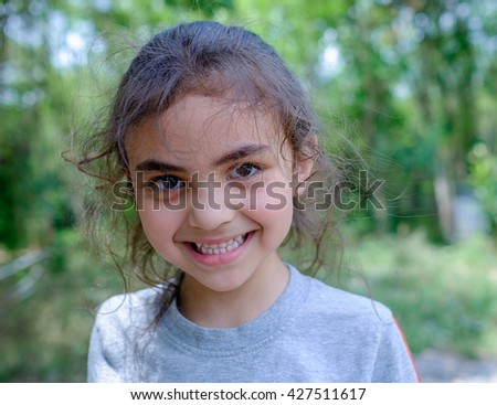 portrait of happy, positive, smiling, playful mixed race asian caucasian girl in park, candid of smiling girl playing in countryside park home, little childhood mixed race girl - stock photo
