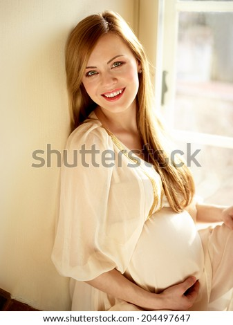 Portrait Of Happy Pregnant Woman Sitting Near Window - stock photo