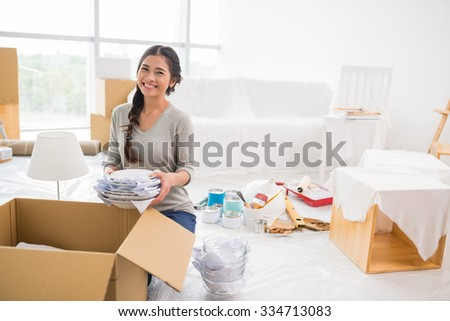 Portrait of happy pretty girl unpacking in her new apartment - stock photo