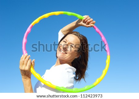 Portrait of happy pretty senior woman exercising with colorful hula hoop, isolated with blue sky as background and copy space. - stock photo