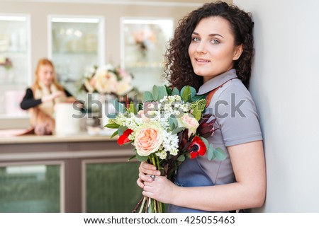 Portrait of happy pretty young woman florist with bouquet of flowers standing in flower shop  - stock photo