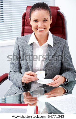 Portrait of happy professional with cup in hand looking at camera with smile in office - stock photo