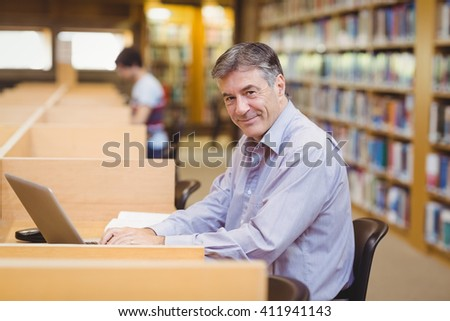 Portrait of happy professor sitting at desk using his laptop in college library - stock photo