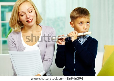 Portrait of happy pupil playing the flute with charming tutor near by - stock photo