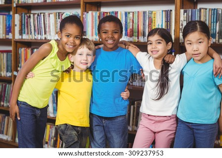 Portrait of happy pupils having arms around in the library in school - stock photo