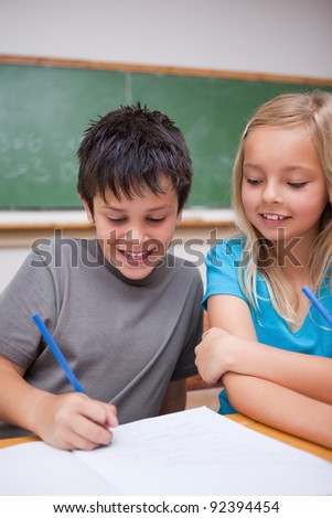 Portrait of happy pupils working together in a classroom - stock photo