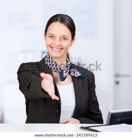 Portrait of happy receptionist offering handshake at counter - stock photo