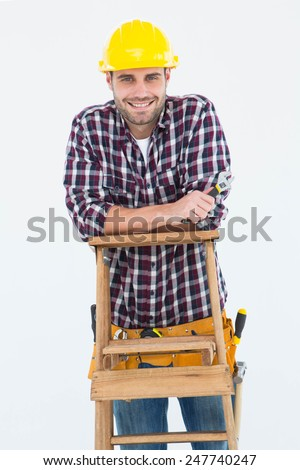 Portrait of happy repairman holding spanner while climbing ladder on white background - stock photo