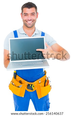 Portrait of happy repairman pointing at laptop on white background - stock photo