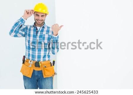 Portrait of happy repairman pointing towards blank billboard on white background - stock photo
