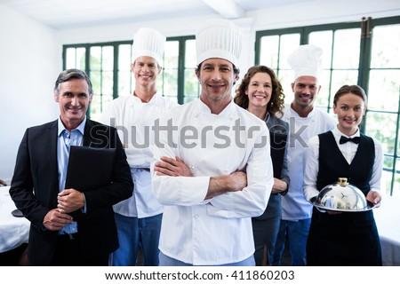 Portrait of happy restaurant team standing together in restaurant - stock photo