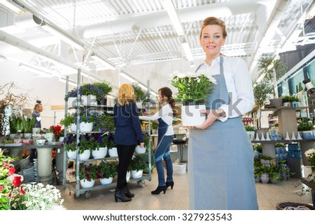 Portrait of happy salesgirl holding flower pot with customer and colleague in background at shop - stock photo