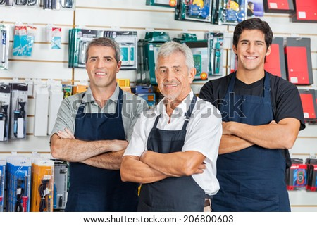 Portrait of happy salesmen standing arms crossed in hardware store - stock photo