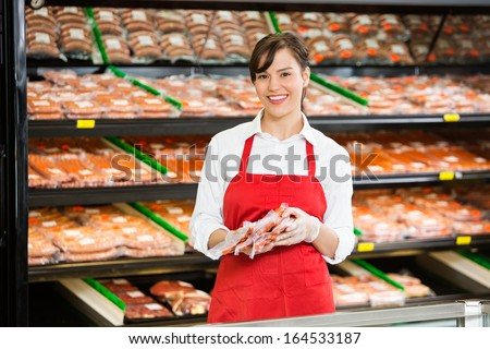 Portrait of happy saleswoman holding meat packages at counter in butcher's shop - stock photo