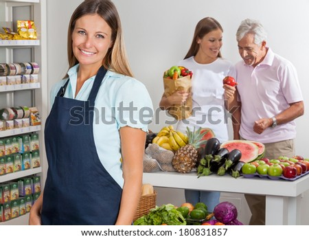 Portrait of happy saleswoman with family shopping in background at supermarket - stock photo
