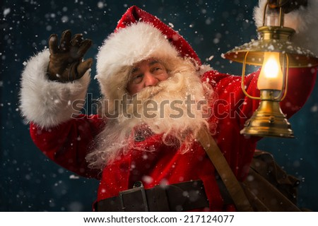 Portrait of happy Santa Claus holding sack with gifts and walking under snowfall with vintage lantern outdoors - stock photo