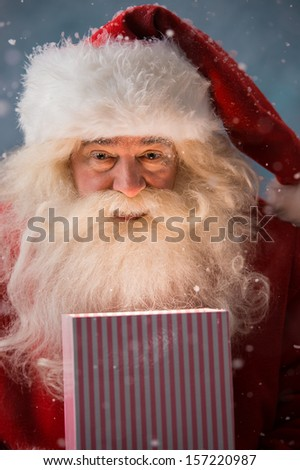 Portrait of happy Santa Claus opening gift box outdoors at North Pole. Magical light from box on his face - stock photo