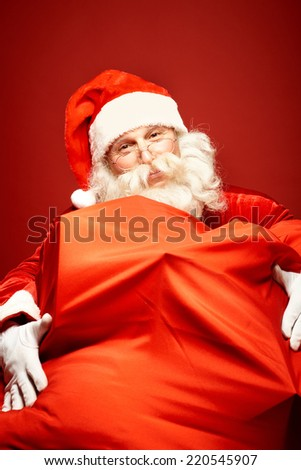 Portrait of happy Santa Claus with gigantic sack full of gifts looking at camera - stock photo