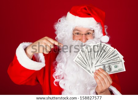 Portrait of happy santa holding dollars over red background - stock photo