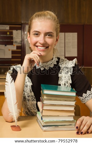 Portrait of happy school girl at her desk - stock photo