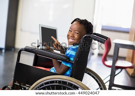 Portrait of happy schoolboy sitting on wheelchair and using digital tablet at school - stock photo