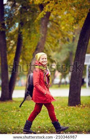 Portrait of happy schoolgirl in casual going to school through park - stock photo