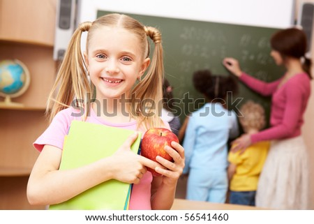 Portrait of happy schoolgirl with copybooks looking at camera - stock photo