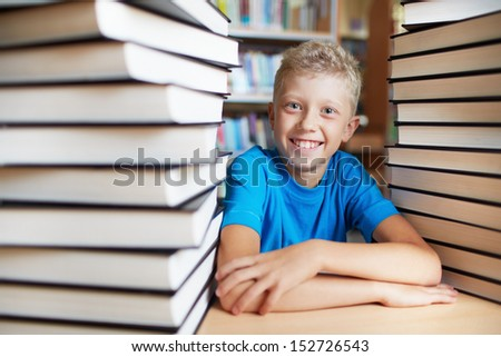 Portrait of happy schoolkid looking at camera surrounded by stacks of books - stock photo