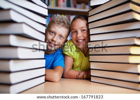 Portrait of happy schoolkids between stacks of books looking at camera - stock photo