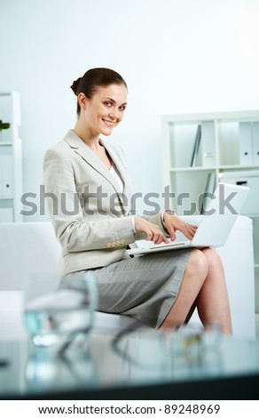 Portrait of happy secretary sitting in office and typing - stock photo