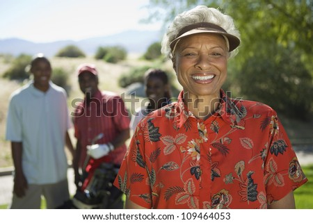 Portrait of happy senior African American woman at golf course with people in background - stock photo