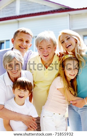 Portrait of happy senior and young couples looking at camera outdoors with new cottage at background - stock photo