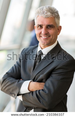 portrait of happy senior businessman with arms crossed - stock photo