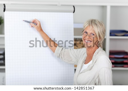 Portrait of happy senior businesswoman pointing with felttip pen on presentation board at office - stock photo