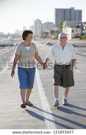 Portrait of happy senior Caucasian couple walking together on embankment - stock photo