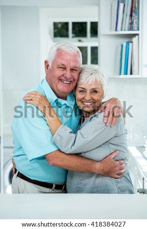 Portrait of happy senior couple embracing at home - stock photo