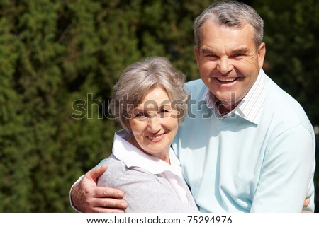 Portrait of happy senior couple embracing each other and looking at camera - stock photo
