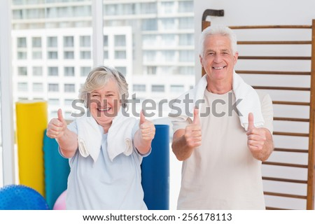 Portrait of happy senior couple gesturing thumbs up in gym - stock photo