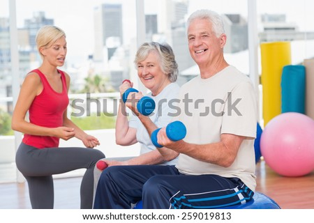 Portrait of happy senior couple lifting dumbbells while instructor guiding them in gym - stock photo