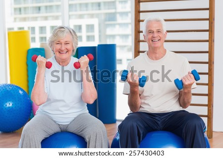 Portrait of happy senior couple lifting dumbbells while sitting on exercise ball at gym - stock photo