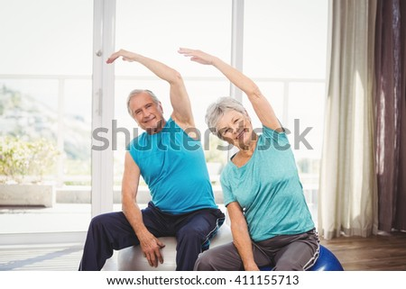 Portrait of happy senior couple performing exercise at home - stock photo