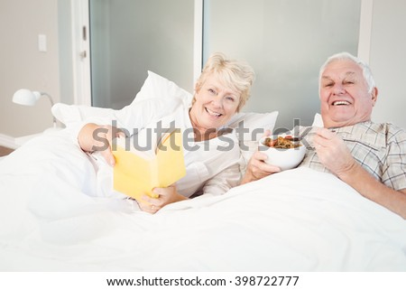 Portrait of happy senior couple reading book in bed at home - stock photo