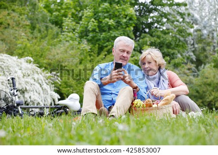Portrait of happy senior couple seated on the grass and relaxing while using their smart phone.  - stock photo