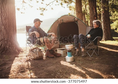 Portrait of happy senior couple sitting in chairs by tent at campsite. Mature man and woman relaxing and talking near a lake on a sunny day. - stock photo