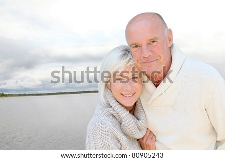 Portrait of happy senior couple standing by a lake - stock photo