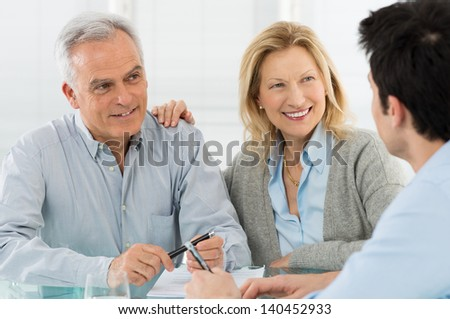Portrait Of Happy Senior Couple Talking With A Young Man - stock photo