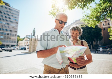 Portrait of happy senior couple using city map for finding their location. Mature couple travelling in a city with a road map. - stock photo
