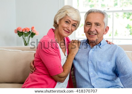 Portrait of happy senior couple with arm around while sitting on sofa - stock photo