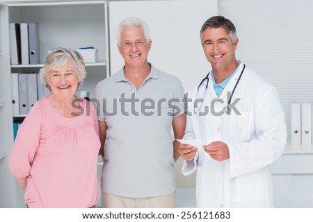 Portrait of happy senior couple with doctor standing in clinic - stock photo