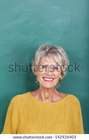 Portrait of happy senior female teacher against chalkboard - stock photo